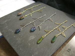 Three pairs of wire earrings, shaped like vines, with glass beads dangling at the end.