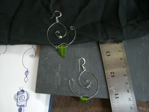 Earrings made with wire shaped into two spirals, with glass beads dangling from them.