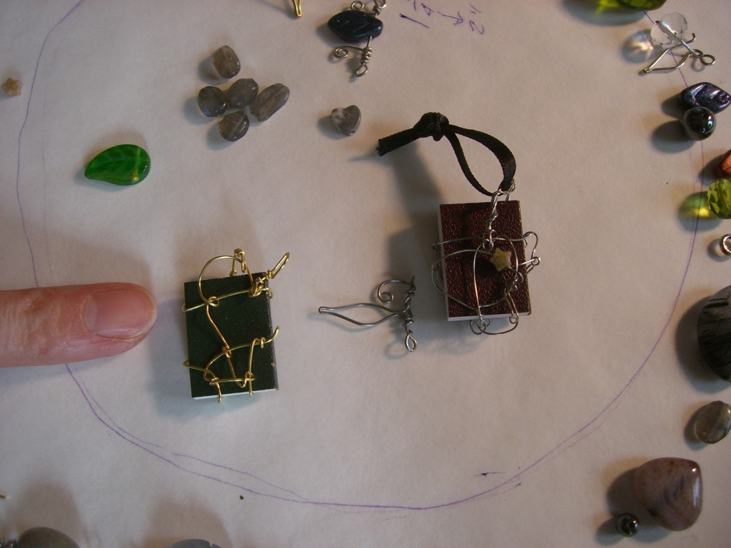 Two TINY BOOKS wrapped in wire, to be used as pendants.